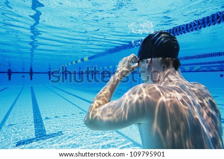 Rear view of a male participant holding breathe underwater - stock photo