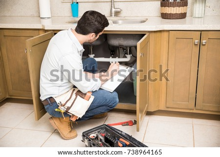 Rear view of a male plumber writing a repair order while crouching in front of a kitchen sink