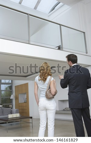 Rear view of a male real estate agent showing woman new home - stock photo