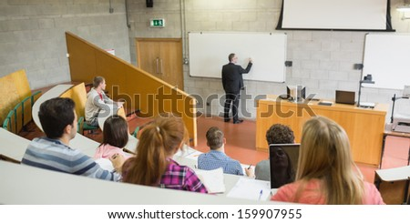 Rear view of a male teacher with students at the college lecture hall - stock photo