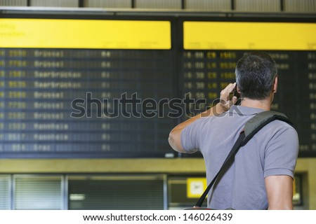Rear view of a male traveler using mobile phone in front of flight status board in airport - stock photo