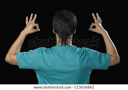 Rear view of a man gesturing OK sign - stock photo