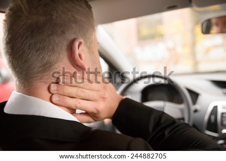 Rear View Of A Man Having Neck Pain While Driving A Car - stock photo