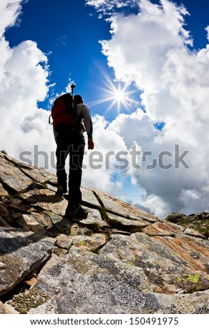 Rear view of a man hiking up a rock hill against a dramatic cloudy sky. Summer season. Vertical shot with large copy-space at the bottom. - stock photo