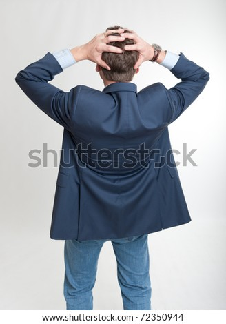 Rear view of a man holding his head in a desperate gesture - stock photo