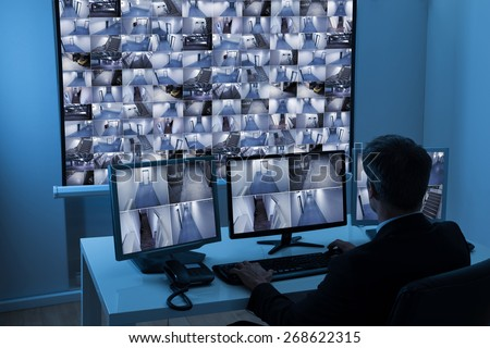 Rear View Of A Man In Control Room Monitoring Multiple Cctv Footage - stock photo