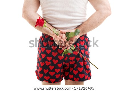 Rear view of a man in heart boxer shorts holding a red rose for his lover behind his back.  White background.   - stock photo