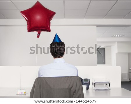 Rear view of a man in party hat by red balloon working alone in office - stock photo
