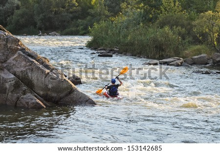 Rear view of a man rafting with kayak on a fast watercourse passing through cliffs and forested areas - stock photo