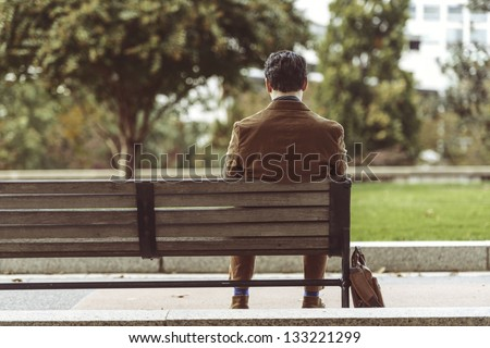 Rear View Of A Man Sitting At Park Bench Waiting