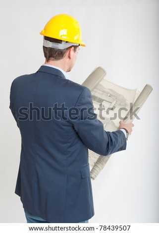 Rear view of a man with a safety helmet consulting blueprints - stock photo