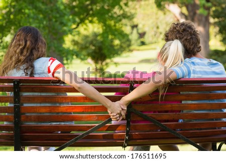 Rear view of a man with girlfriend while holding hands with another woman in the park - stock photo