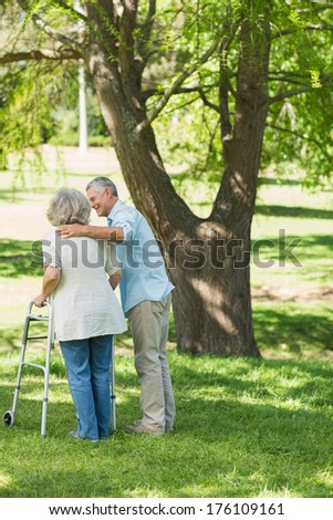 Rear view of a mature man assisting woman with walker at the park - stock photo