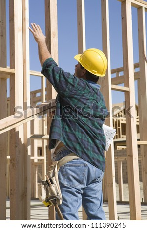 Rear view of a middle aged foreman working at a construction site - stock photo