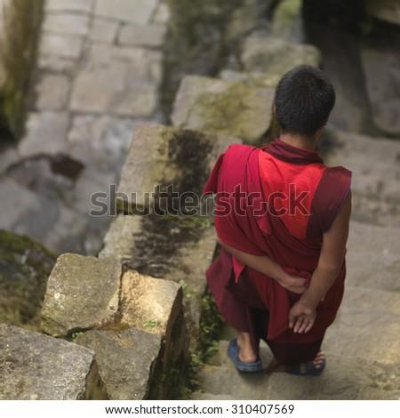 Rear view of a monk moving down steps at Tango Goemba, Thimphu, Bhutan - stock photo