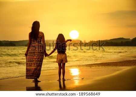 Rear view of a mother and daughter standing on the beach - stock photo