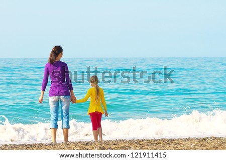 Rear view of a mother and teenage daughter standing on the beach - stock photo