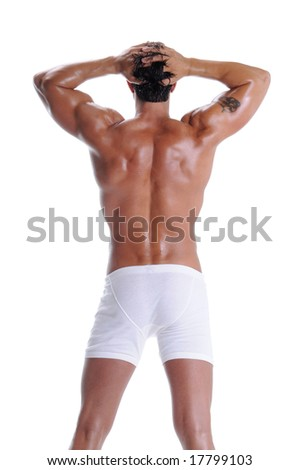 Rear view of a muscular young man standing bare chested in white boxer brief style underwear - stock photo