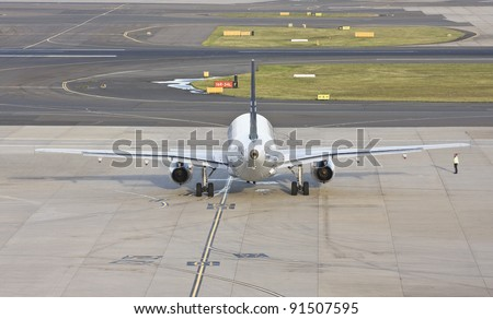 Rear view of a passenger jet plane preparing to enter into runway in late afternoon - stock photo