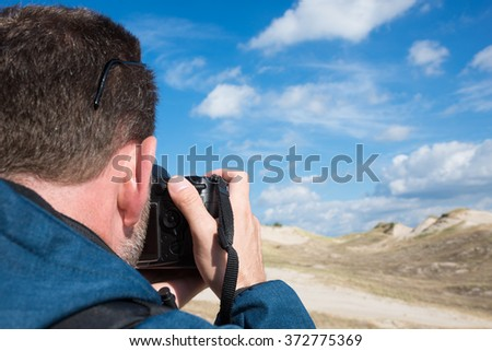 Rear view of a photographer taking pictures of sand and sky landscape on sunny day - stock photo