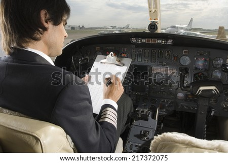 Rear view of a pilot holding a clipboard in the cockpit of a private airplane - stock photo