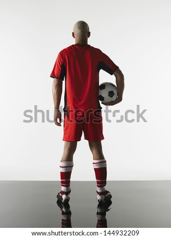 Rear view of a player with football in hand against white background - stock photo