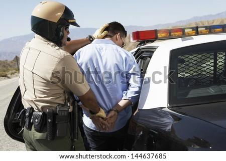 Rear view of a police officer guiding apprehended man into police car - stock photo
