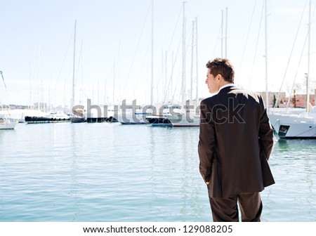 Rear view of a powerful businessman standing by expensive sailing boats and yachts in a coastal city, contemplating the views. - stock photo