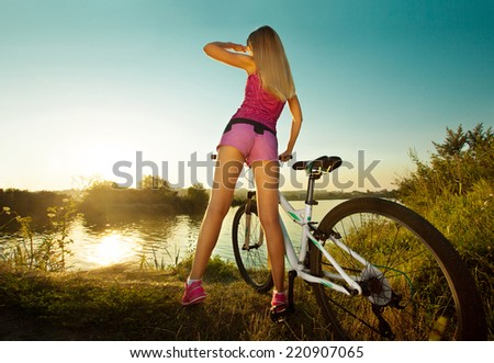 Rear view of a pretty woman on bicycle relaxing at Sunset. Active Leisure Concept. Healthy lifestyle. - stock photo