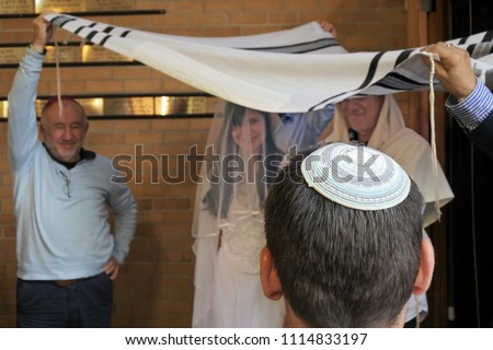 Rear view of a Rabbi belssing Jewish bride and a bridegroom under a chupa (canopy made out of tallit that represents a Jewish home) in a synagog a on their wedding day after Conversion to Judaism.