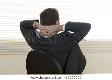 Rear view of a relaxed businessman with hands behind his head - stock photo