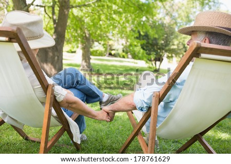 Rear view of a relaxed mature couple sitting in deck chairs at the park - stock photo