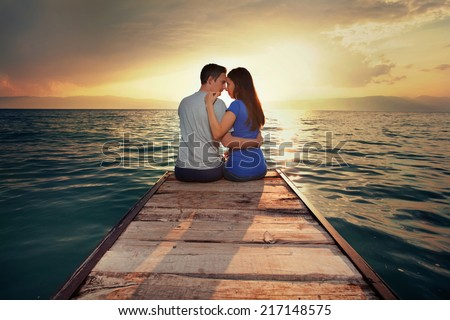 Rear view of a romantic young couple sitting on a jetty at sunset. - stock photo