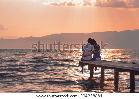 Rear view of a romantic young couple sitting on the pier enjoying  stunning sunset - stock photo