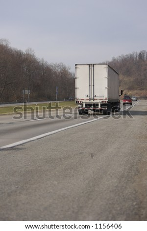 Rear View of a Semi Truck on the Highway - stock photo