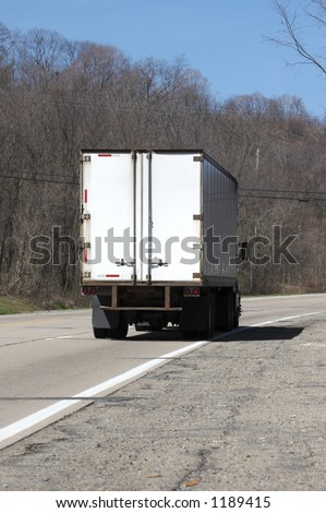 Rear View of a Semi Truck on the Road - stock photo