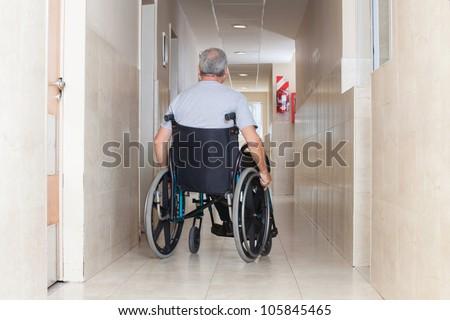 Rear view of a senior man sitting in a wheelchair at hospital corridor - stock photo
