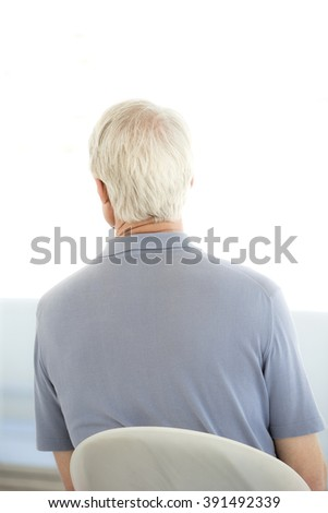 Rear view of a senior man waiting on a chair - stock photo