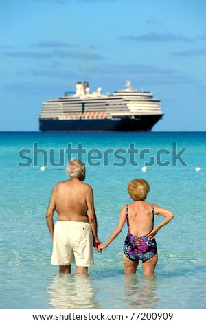 Rear view of a seniors couple holding hands, walking on the beach and watching cruise ship