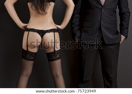 Rear view of a sexy young woman in lingerie and a businessman. Concept about work and pleasure - stock photo