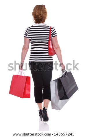 Rear view of a smartly dressed woman carrying shopping bags, isolated on a white background. - stock photo