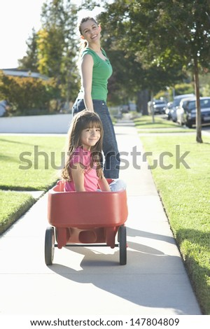 Rear view of a smiling mother pulling daughter in trolley on pathway