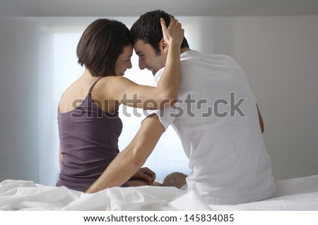 Rear view of a smiling young couple sitting and embracing in bed - stock photo