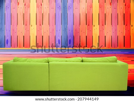 Rear view of a sofa against colorful wall. - stock photo