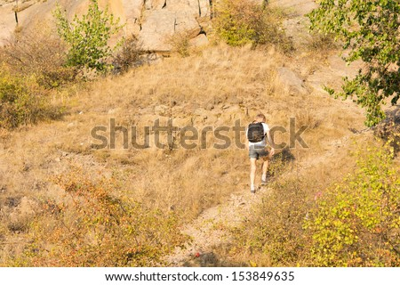 Rear view of a solitary man hiking on a mountain path in a hot day of summer - stock photo