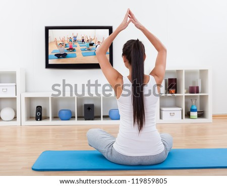 Rear view of a spiritual young woman sitting on a mat meditating at home while watching - stock photo