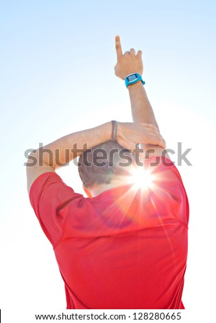 Rear view of a sports man wearing a red shirt and holding one arm up against a deep blue sky with sun rays filtering through his neck. - stock photo