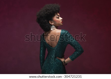 Rear View of a stylish young African American woman in an elegant green evening dress against maroon background. - stock photo