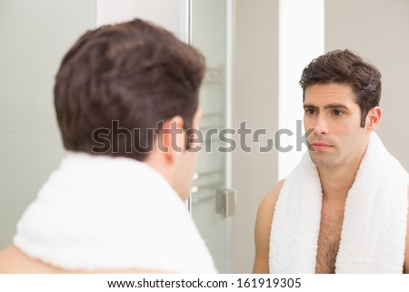 Rear view of a tensed young man looking at self in mirror in the bathroom - stock photo