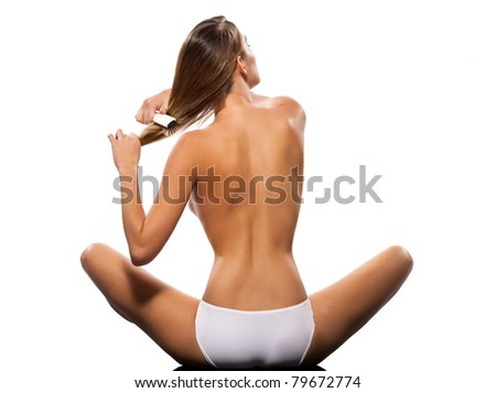 Rear view of a topless slim woman brushing hair on isolated white background - stock photo